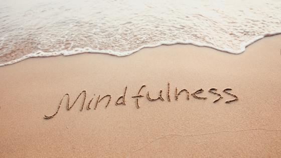 Mindfulness-means-to-navigate-uncertainty written on the beach
